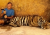 Lee Daniels sits next to a full-grown tiger, while holding its tail.