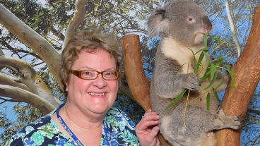 White stands next to a Koala bear while on a trip to Australia