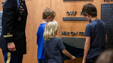 Three of the Taylor children unveil their father's name on BYU's Memorial Wall.