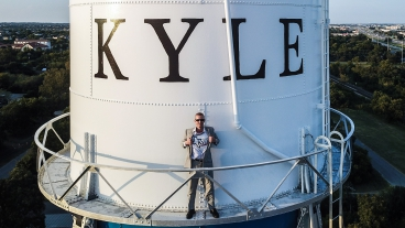 Sellers in front of Kyle, Texas, water tower