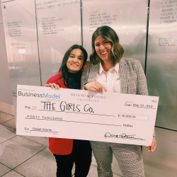 Zoia Ali and Taimi Kennerly pose with a $40,000 check after Girls Co. won the International Business Model Competition