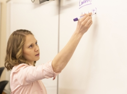 A female writes an equation on a whiteboard