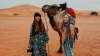 Kylie Chenn and blonde woman pose holding a rope attached to a camel. They are standing in front of a vast empty landscape of orange sand cloudy sky in the Sahara desert