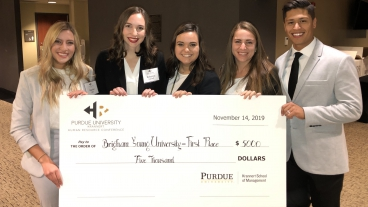 The five members of the BYU team pose with a large check for $5,000. There are four women, one blonde, the other three brunette, and one male.