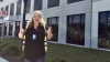 Nichole Rohrbaugh gives two thumbs up in front of large building that reads Amazon Fulfillment.