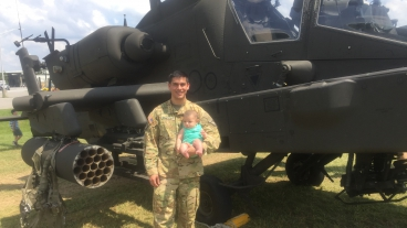 Trevor Findlay and his son in front of an AH-64 Apache helicopter.