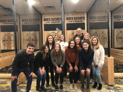 Group photo with Mary Kay Lloyd with group of BYU students standing in front of targets at at Heber Hatchets in Provo.