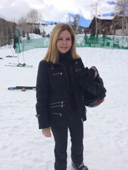 Mary Kay Lloyd standing in front of the snowy ski slopes at Deer Valley Resort while wearing her ski gear.